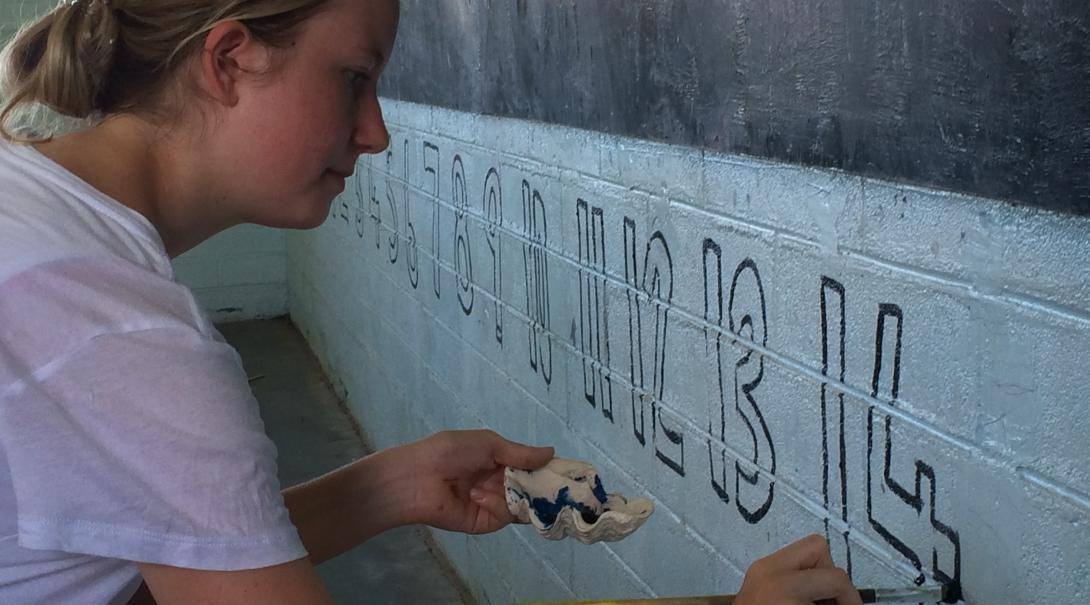 A Care volunteer in Samoa revitalises a classroom by painting numbers